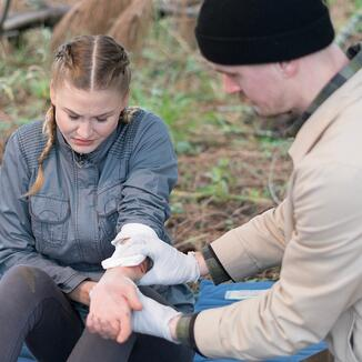 Woman with arm wound receiving first aid from man